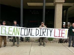 4 people holding a banner reading &quot;Clean Coal Dirty Lie!&quot; outside the ARIES conference at the Marriot in Charleston